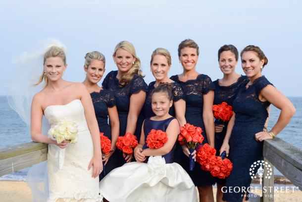 A Beachy Bridal Party Poses In Navy Blue Dresses With Orange Flowers