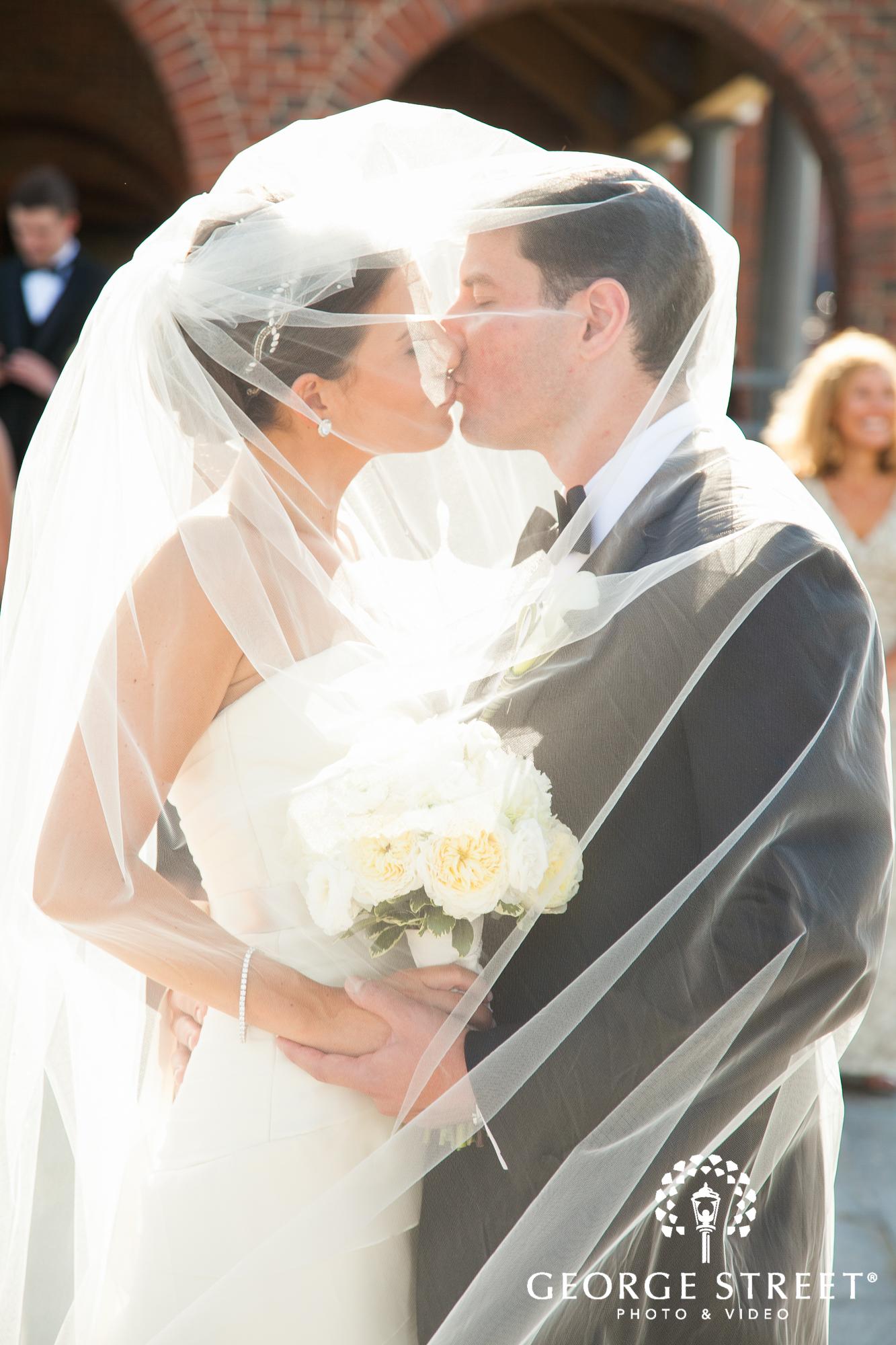 bride and groom kissing under veil 2