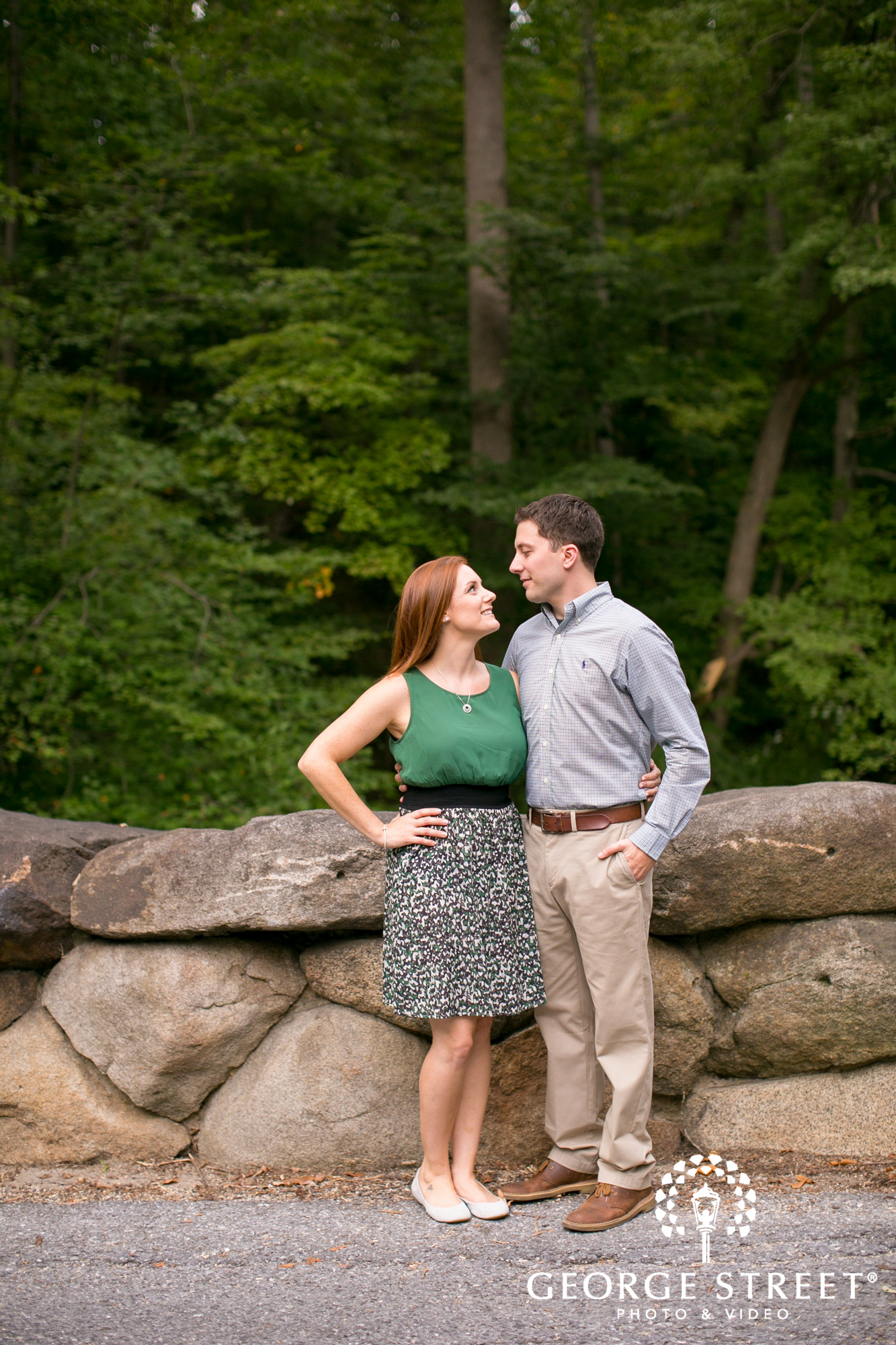 couple by rural stone wall summer engagement
