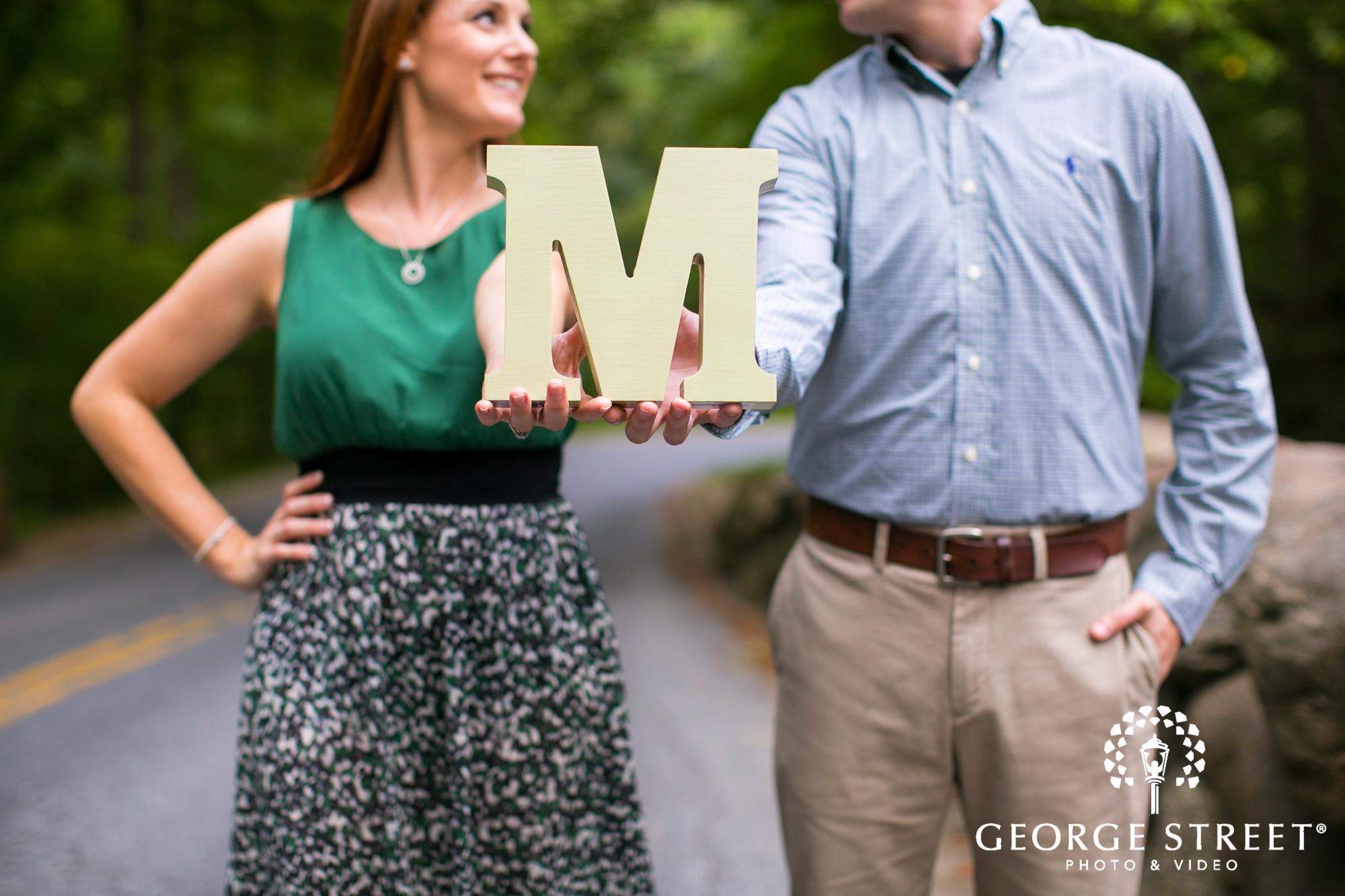 couple holding letter engagement portrait