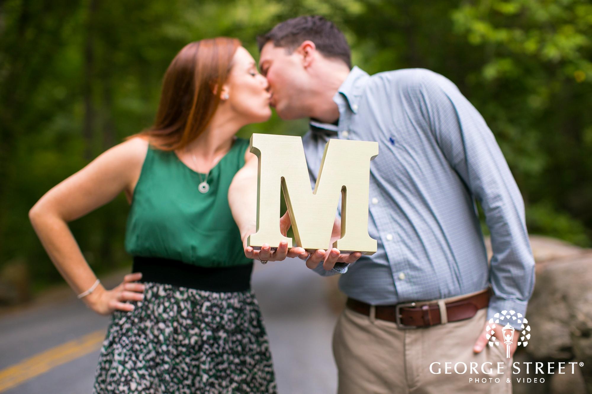 couple kissing behind letter rural portrait