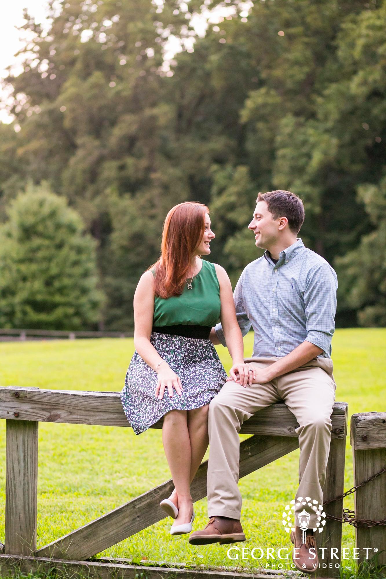couple sitting on wooden fence engagement portrait