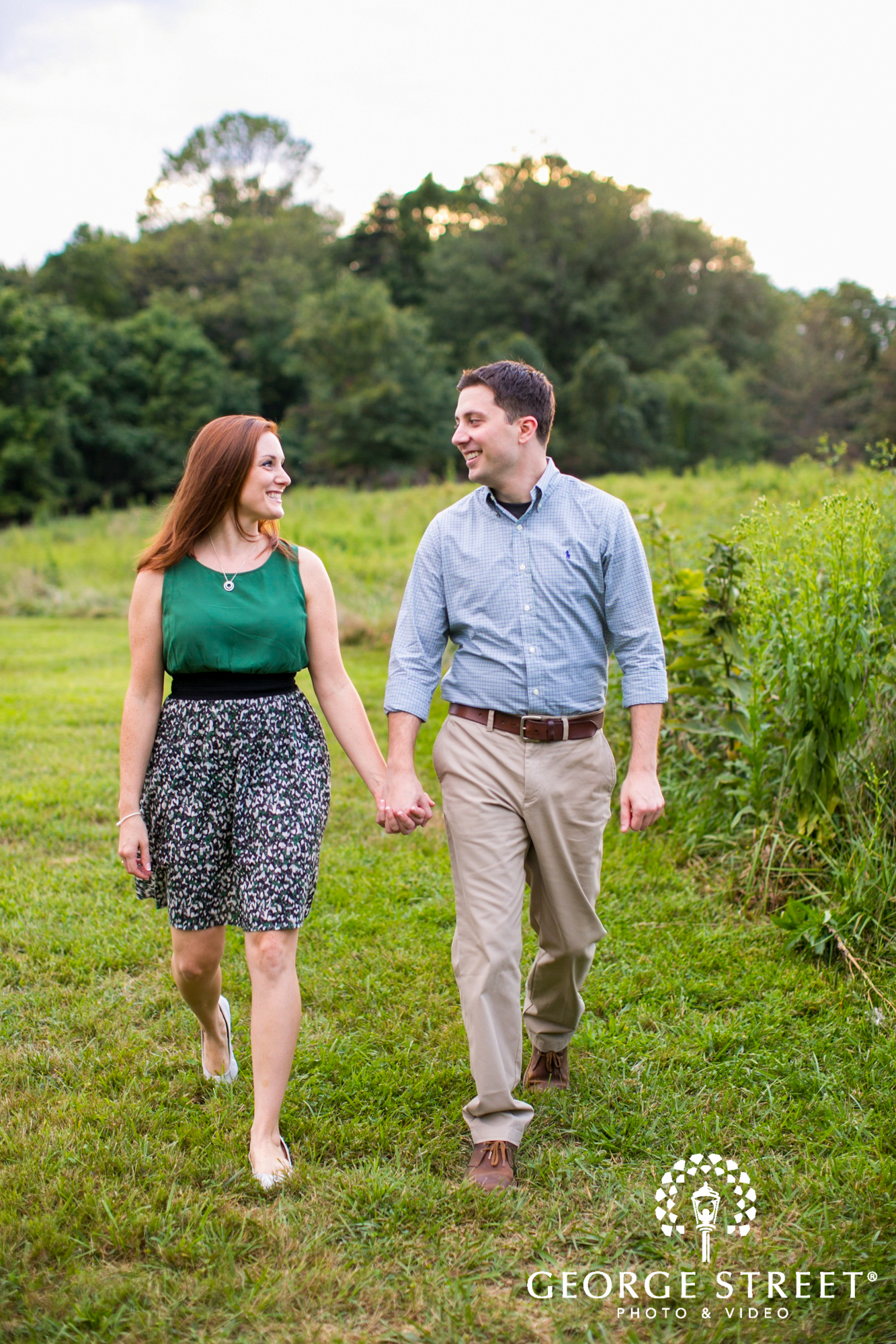 couple walking through field rural engagement portrait
