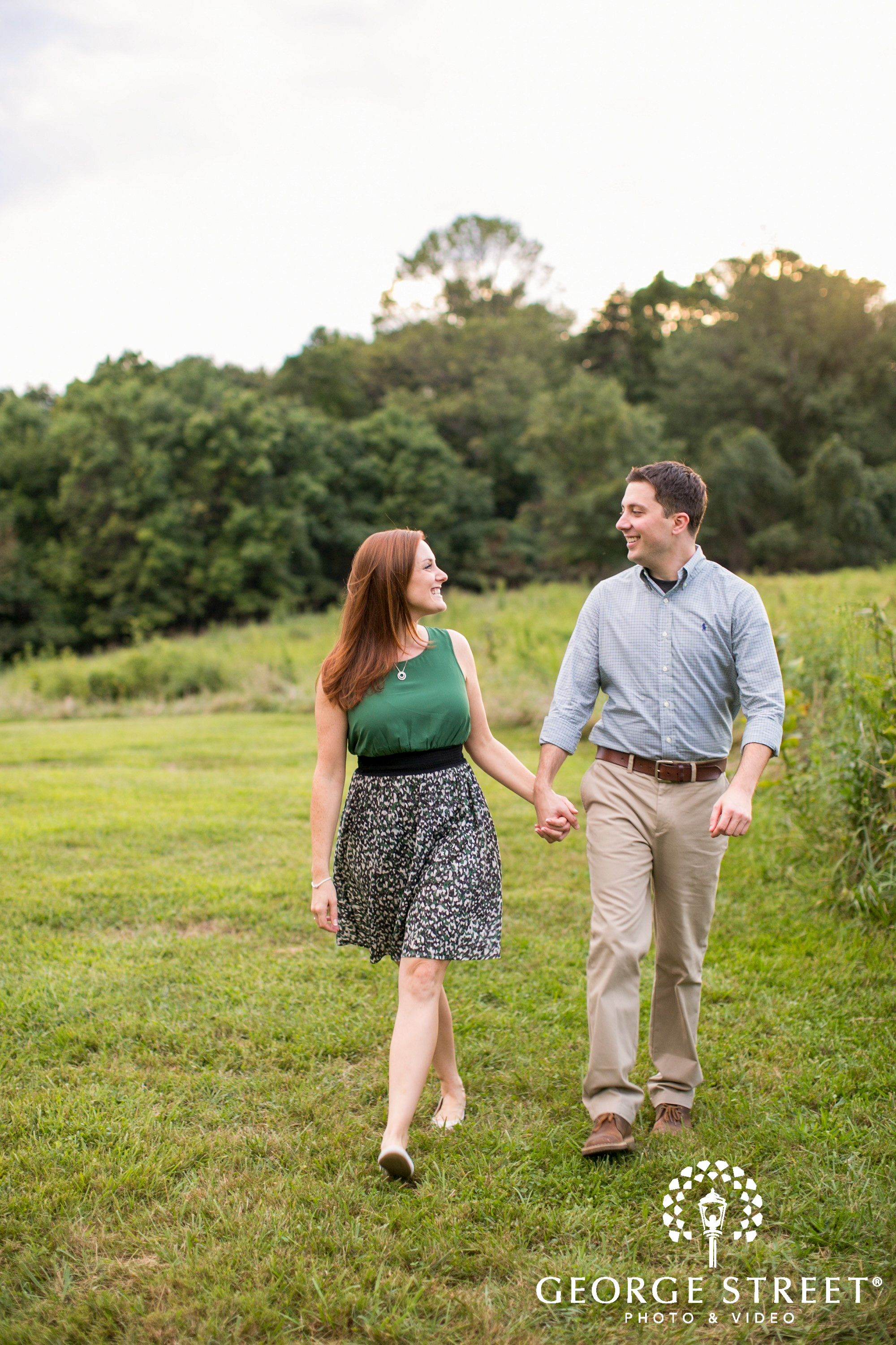 engaged couple holding hands in field