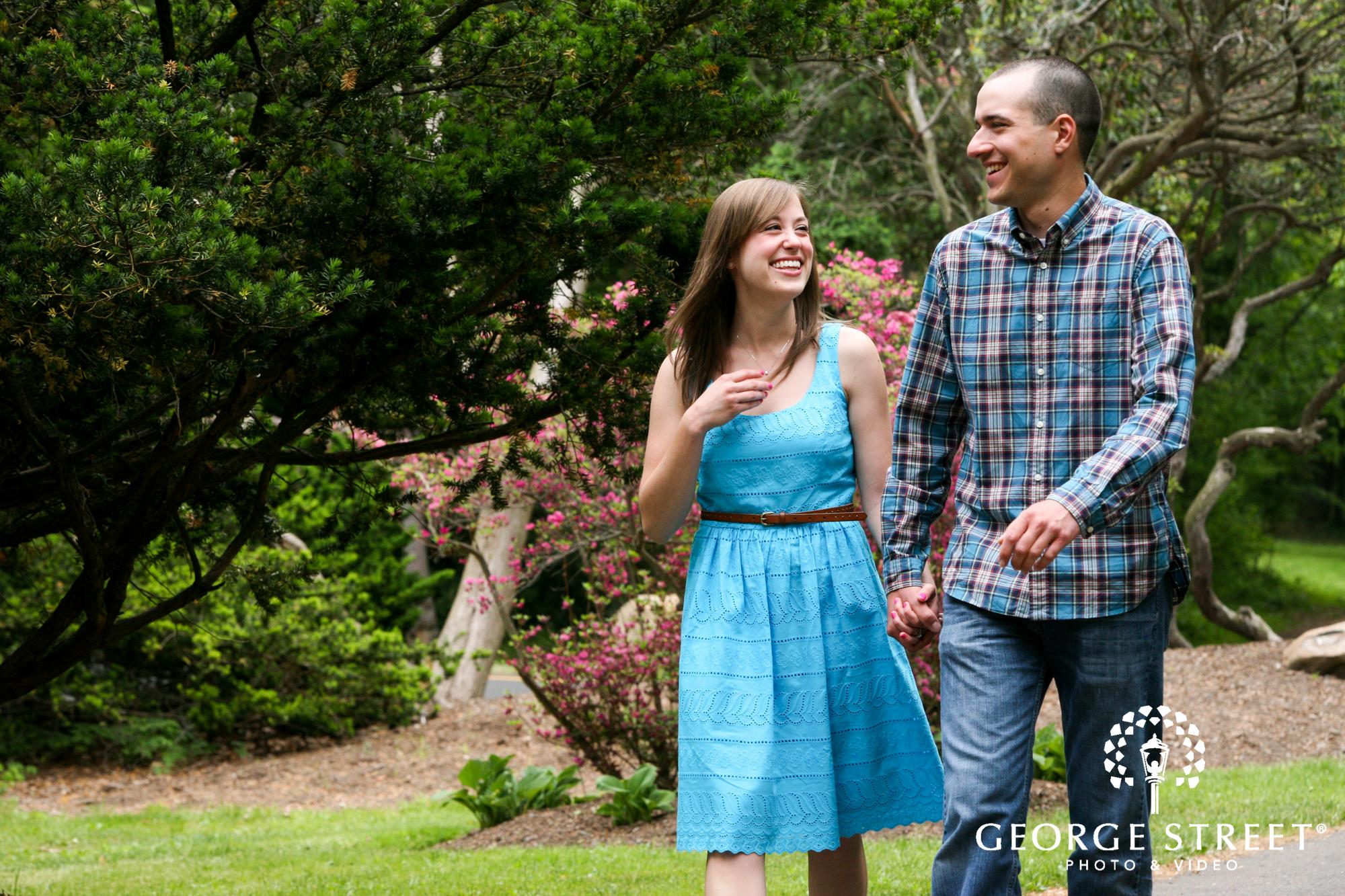 candid couple walking in elizabeth park conservancy engagement portrait
