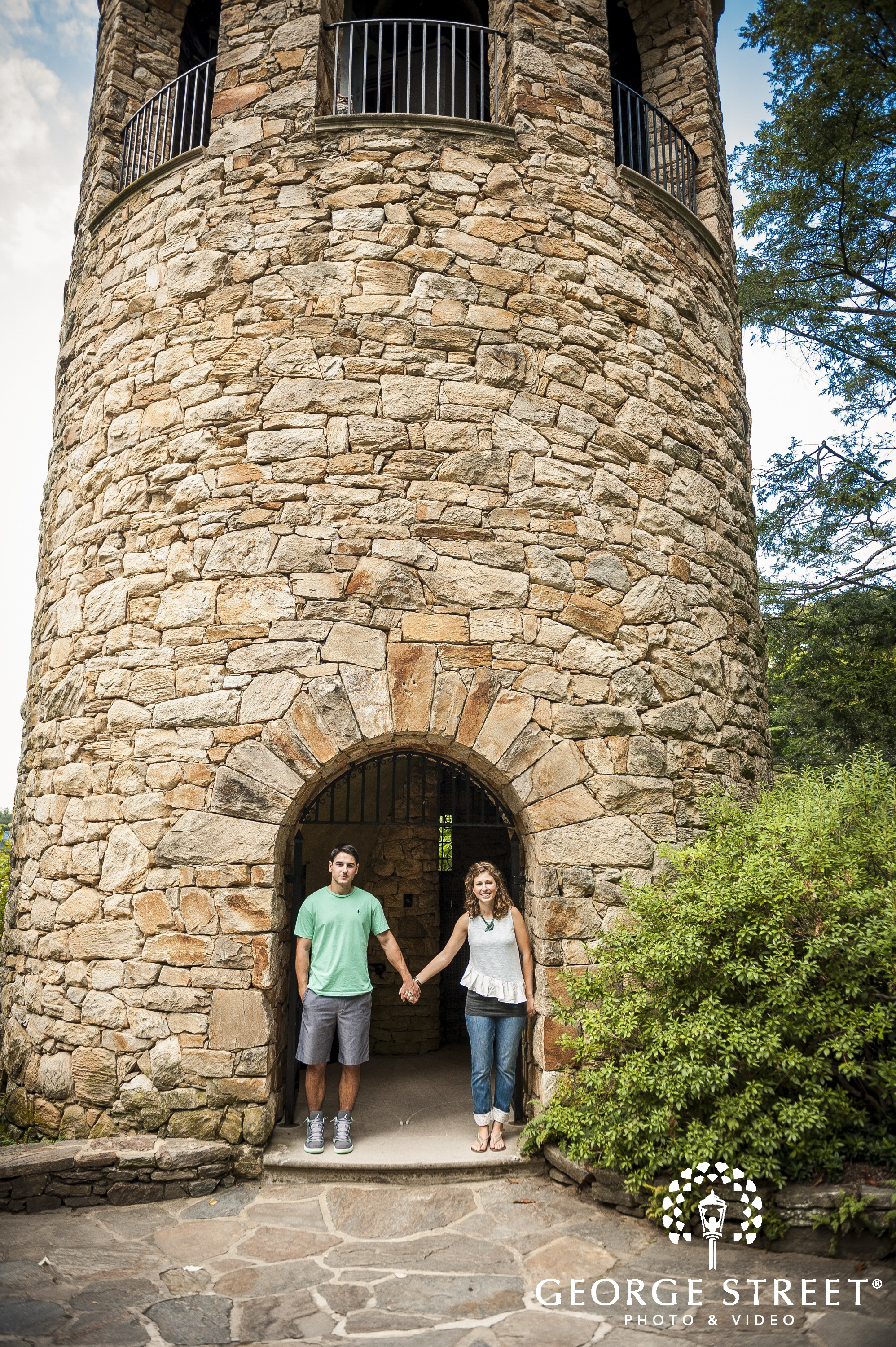 couple holding hands in front of stone lighthouse