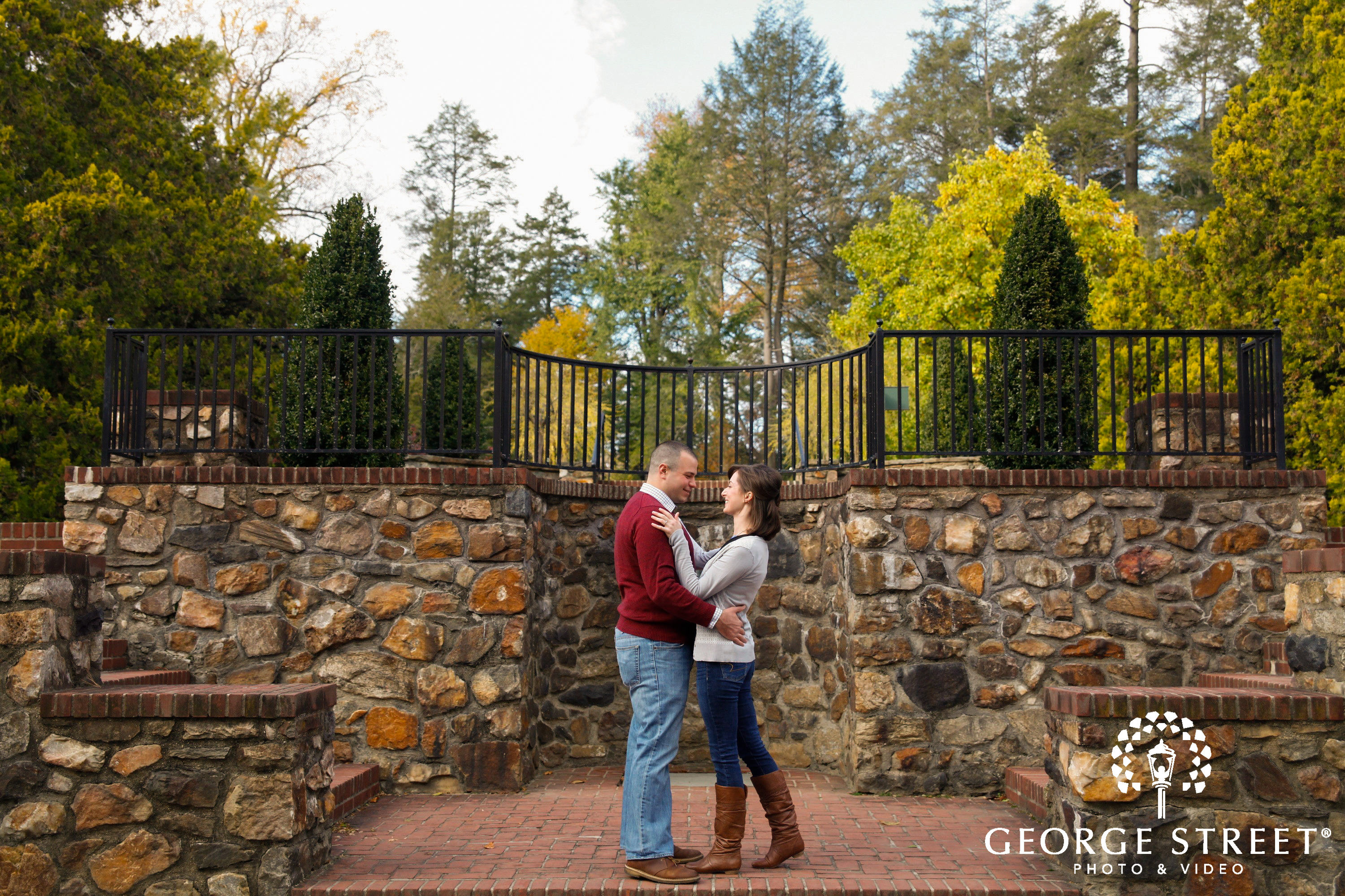 couple hugging in front of stone wall