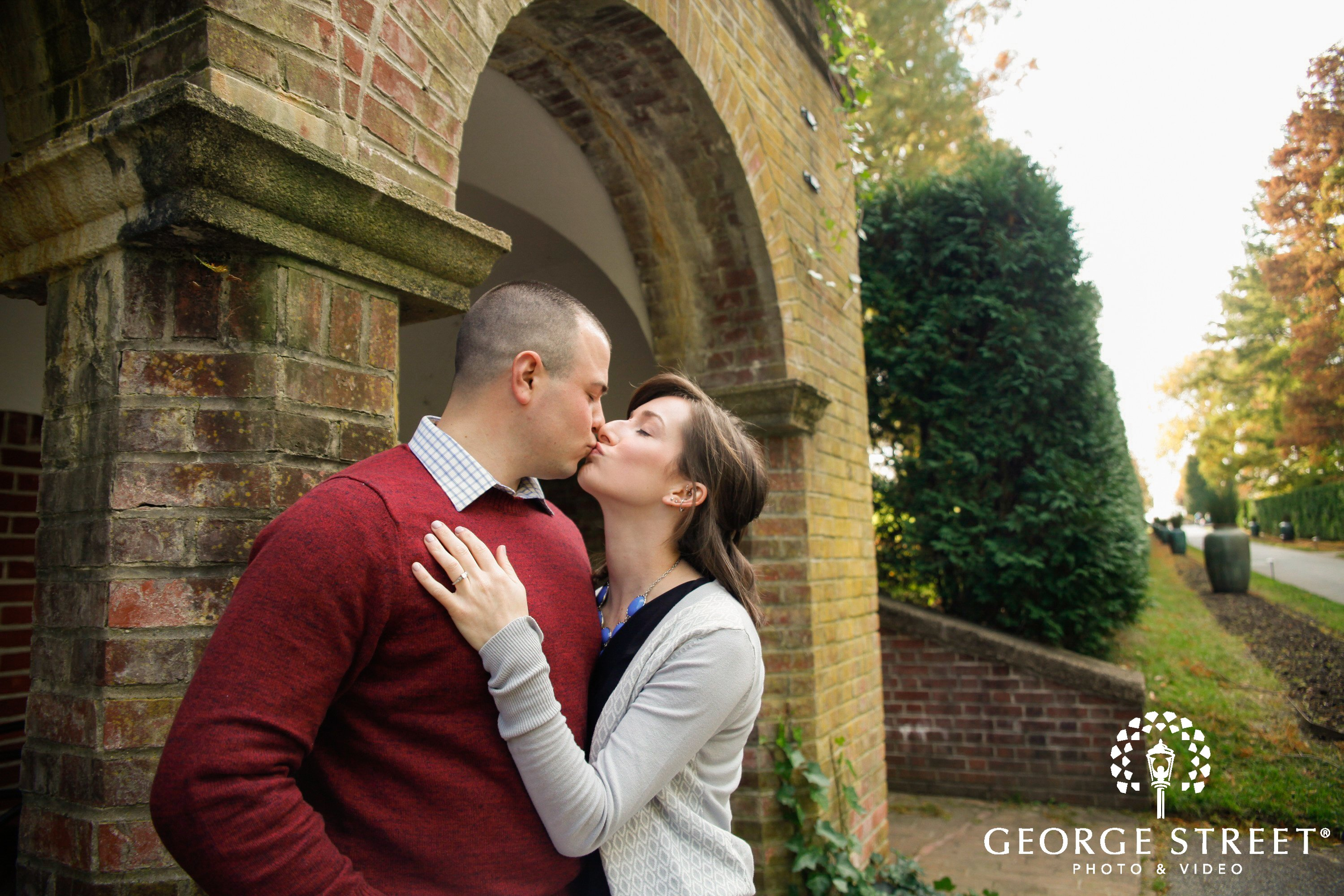 couple kissing in front of brick building