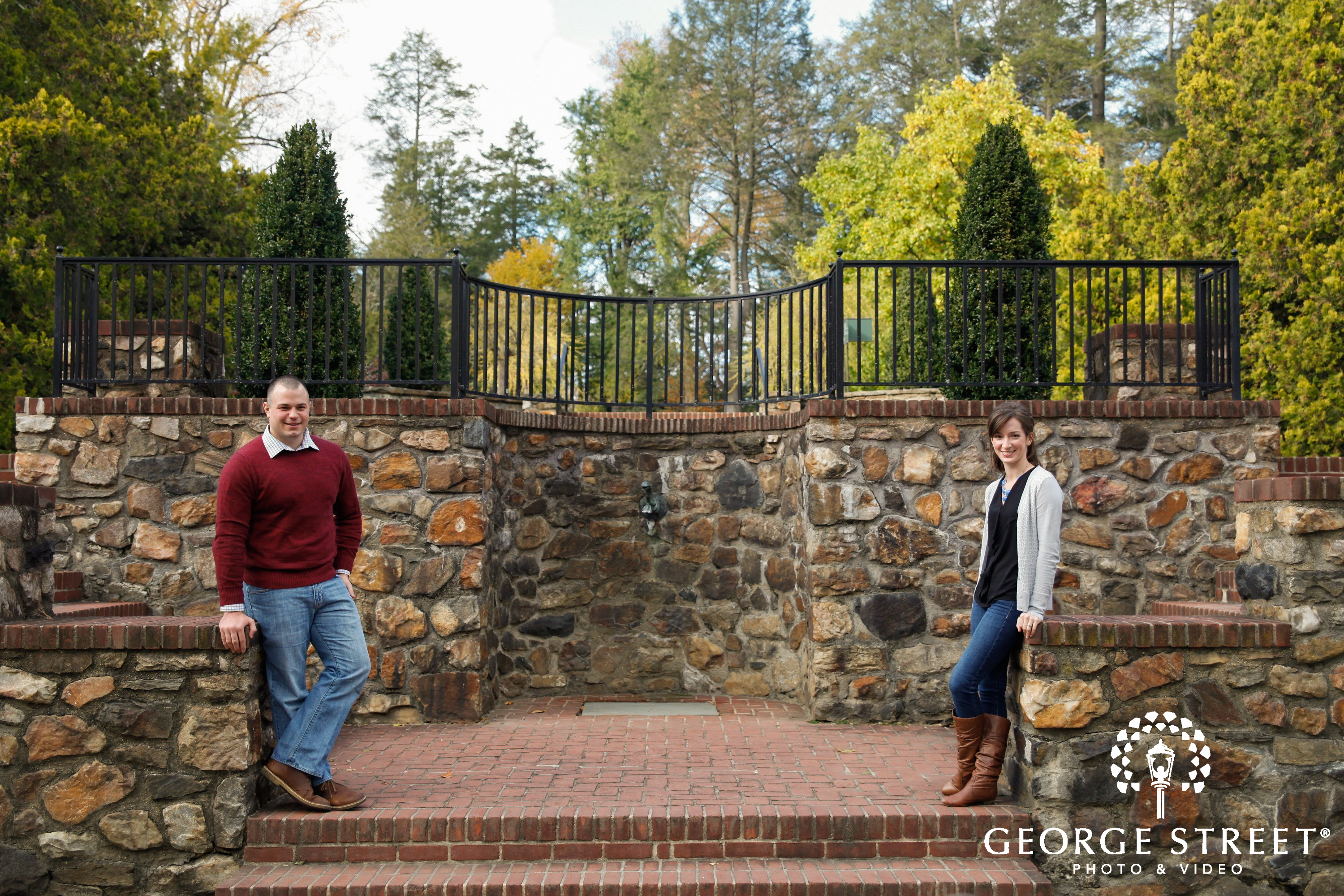 couple posing in front of stone wall