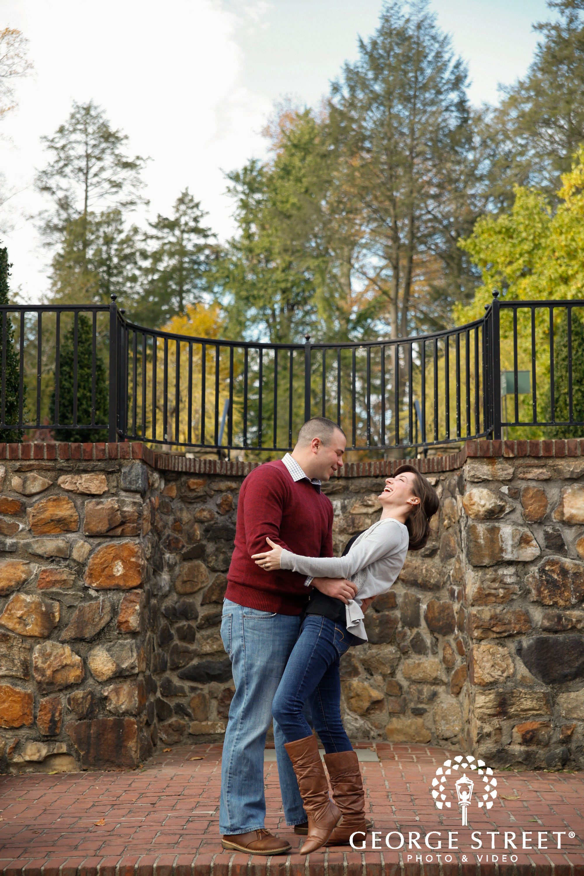 laughing couple in front of stone wall