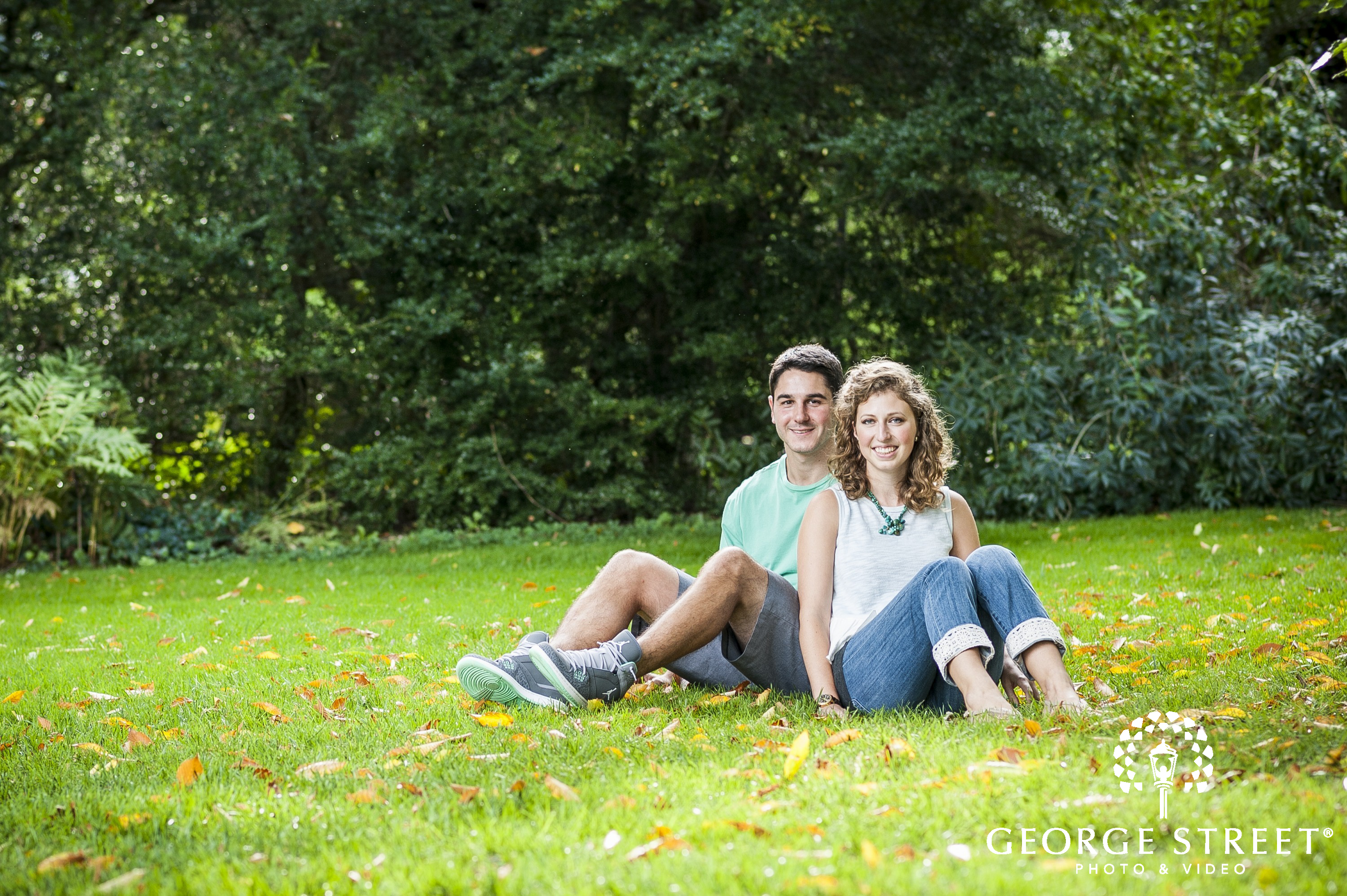 young couple sitting on lawn in park