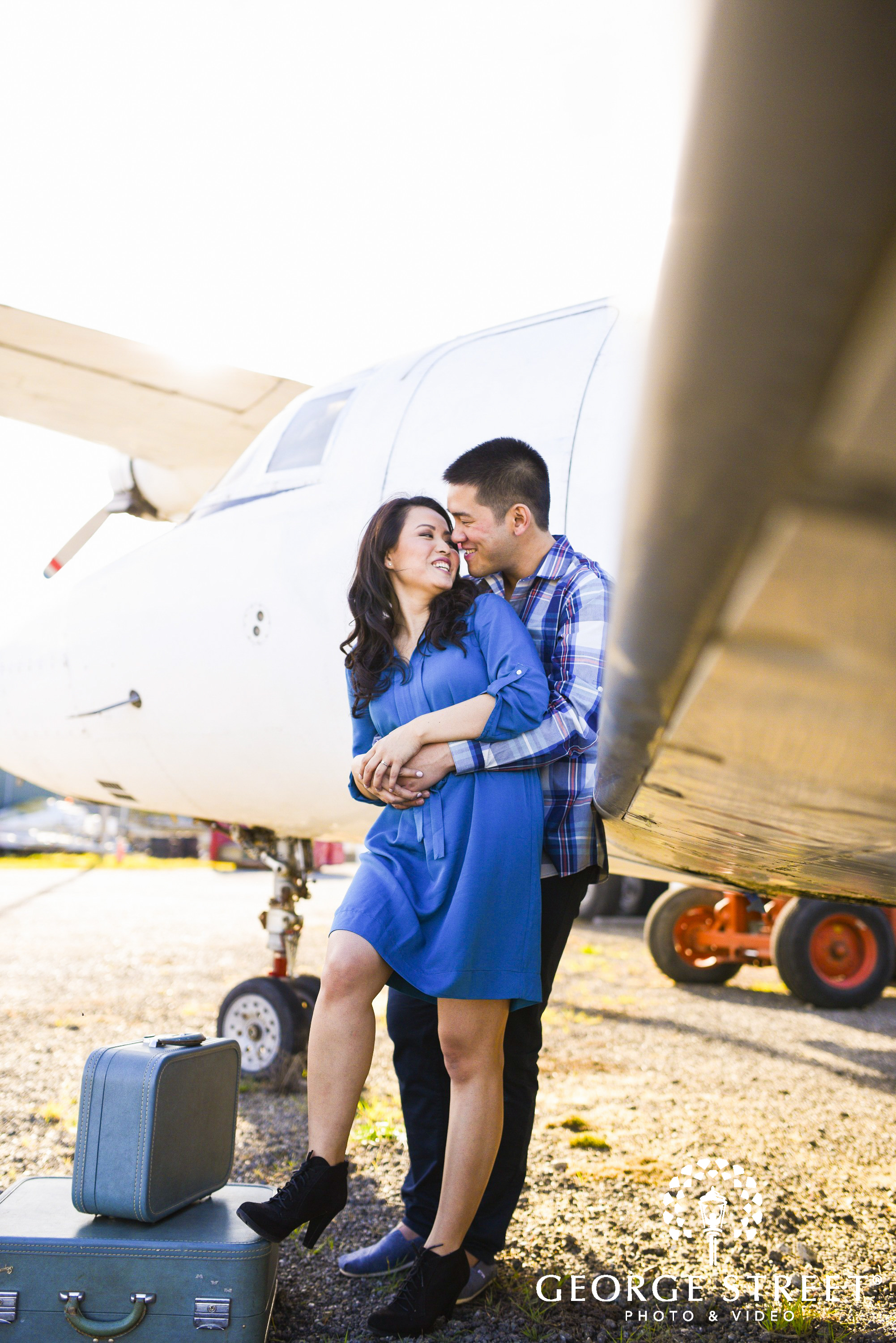 couple posing by airplane with luggage