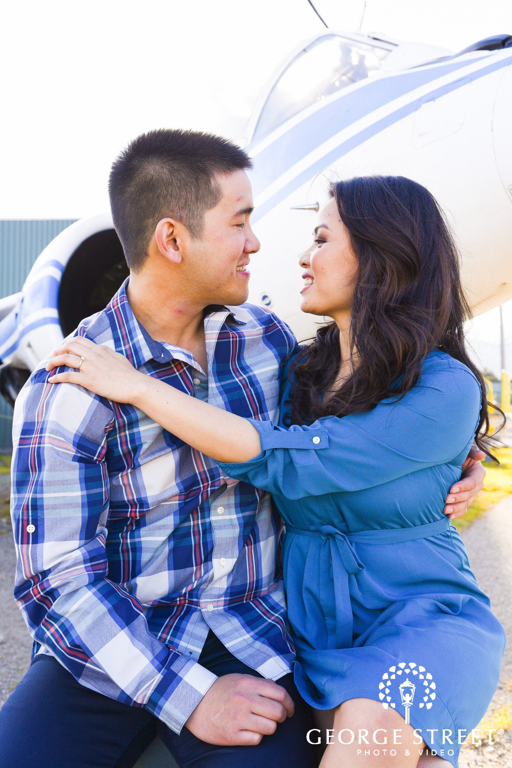 cute young couple at airport in front of airplane