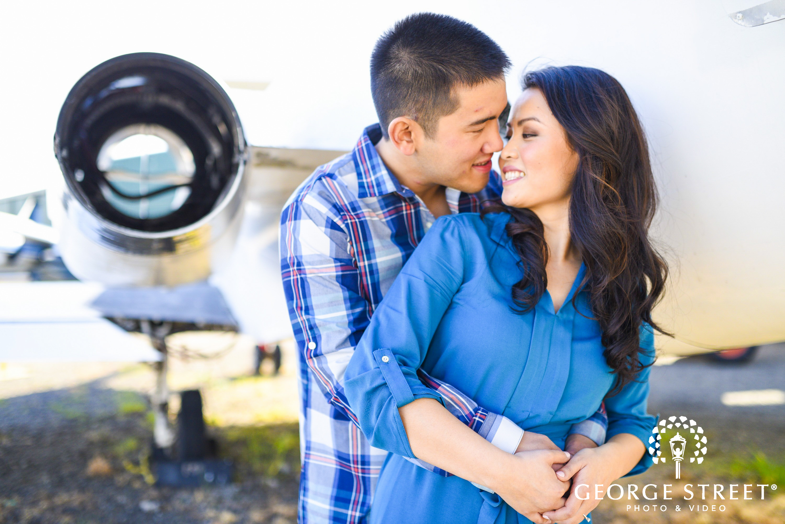 young couple kissing in front of airplane