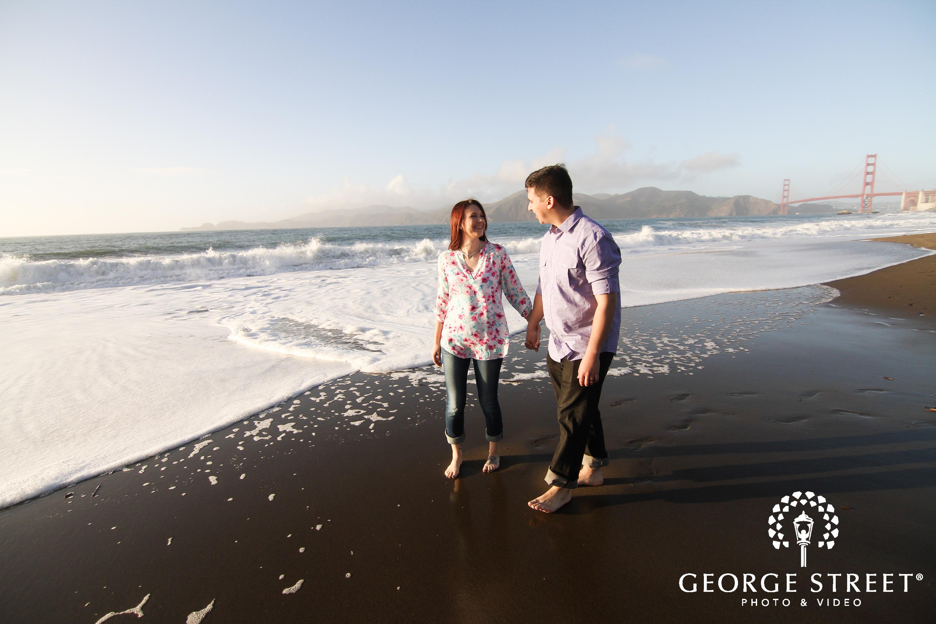 couple holding hands walking in ocean