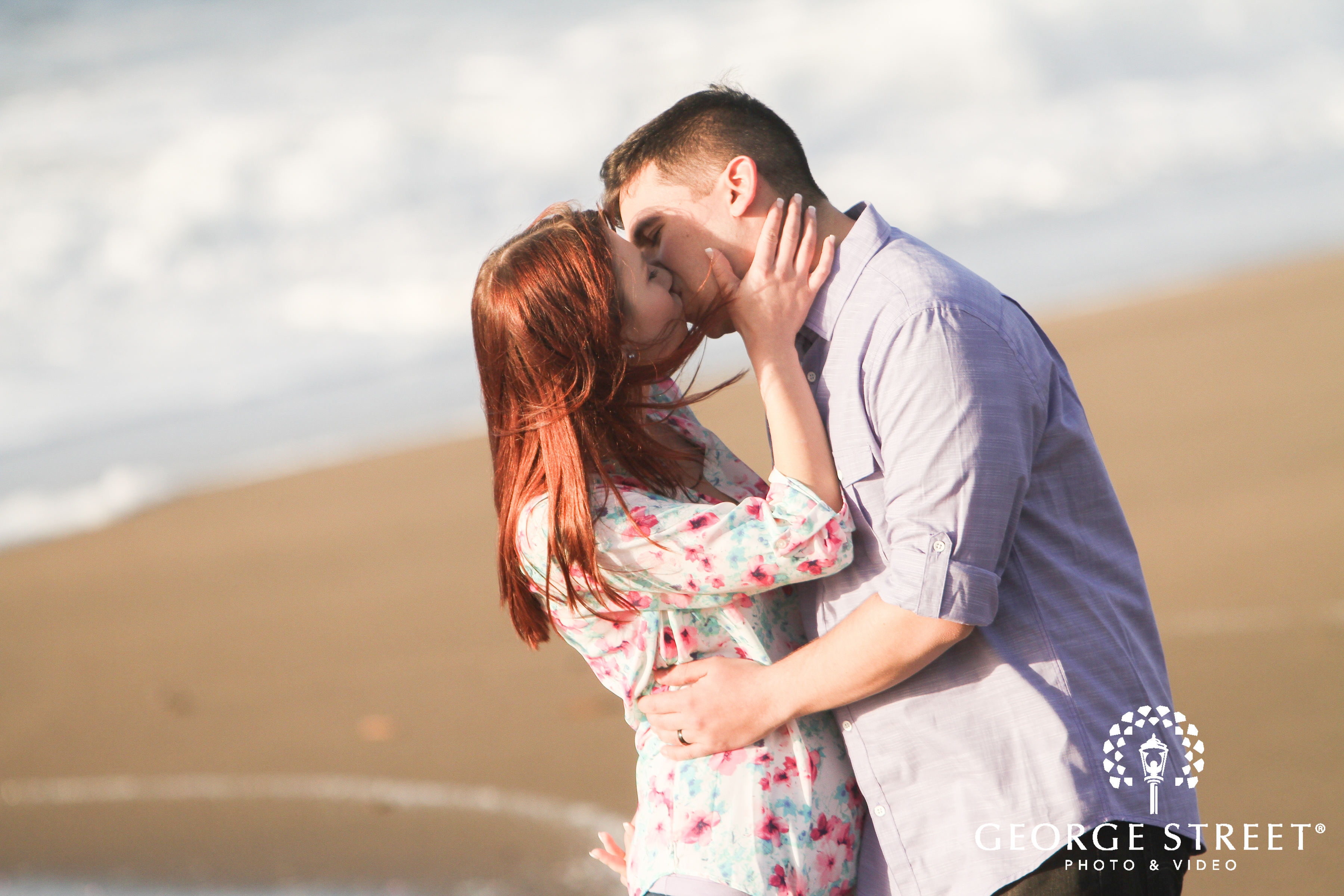 couple kissing at beach engagement