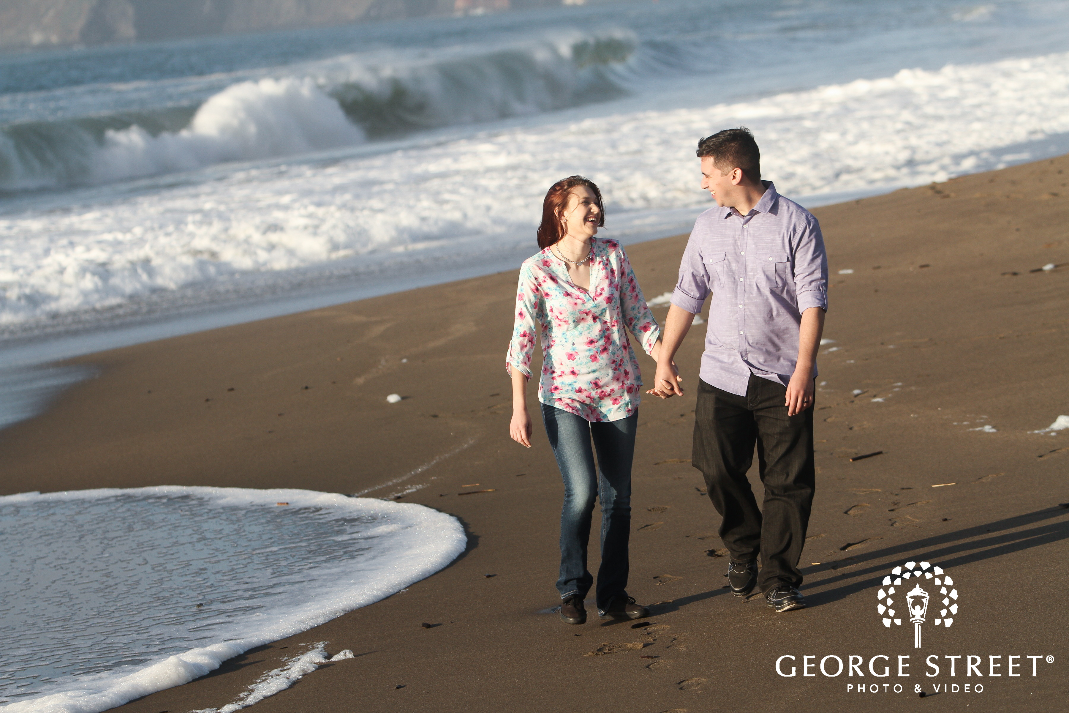 engaged couple walking down the beach