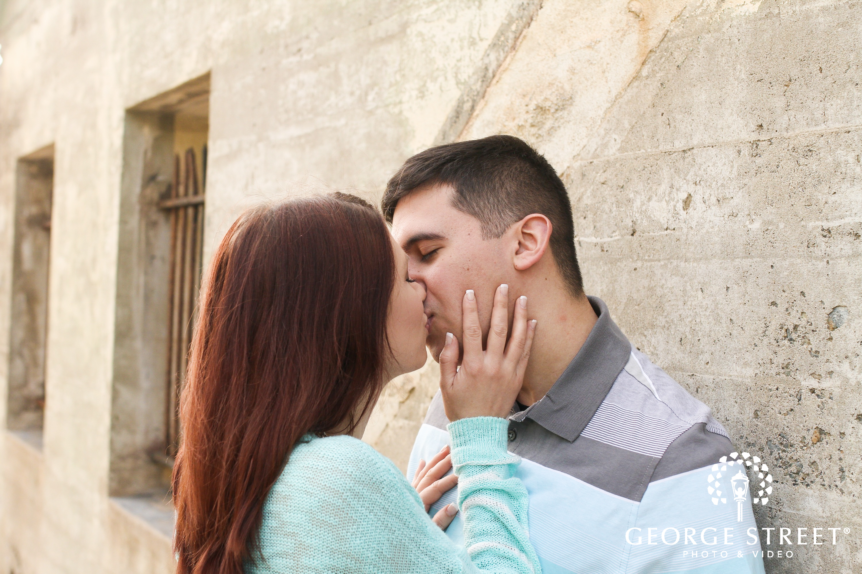 couple kissing against wall