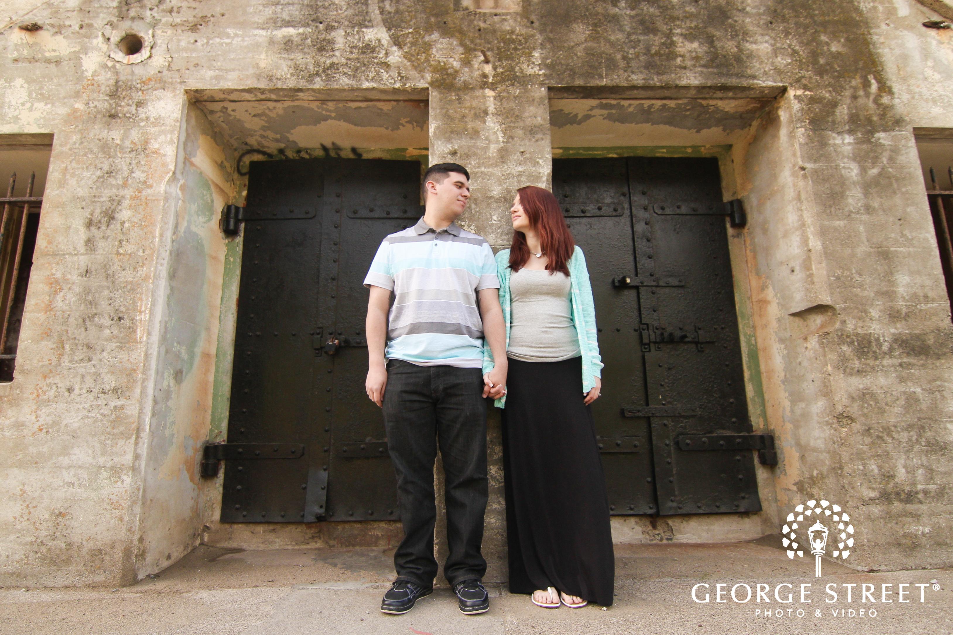couple posing in front of double doors