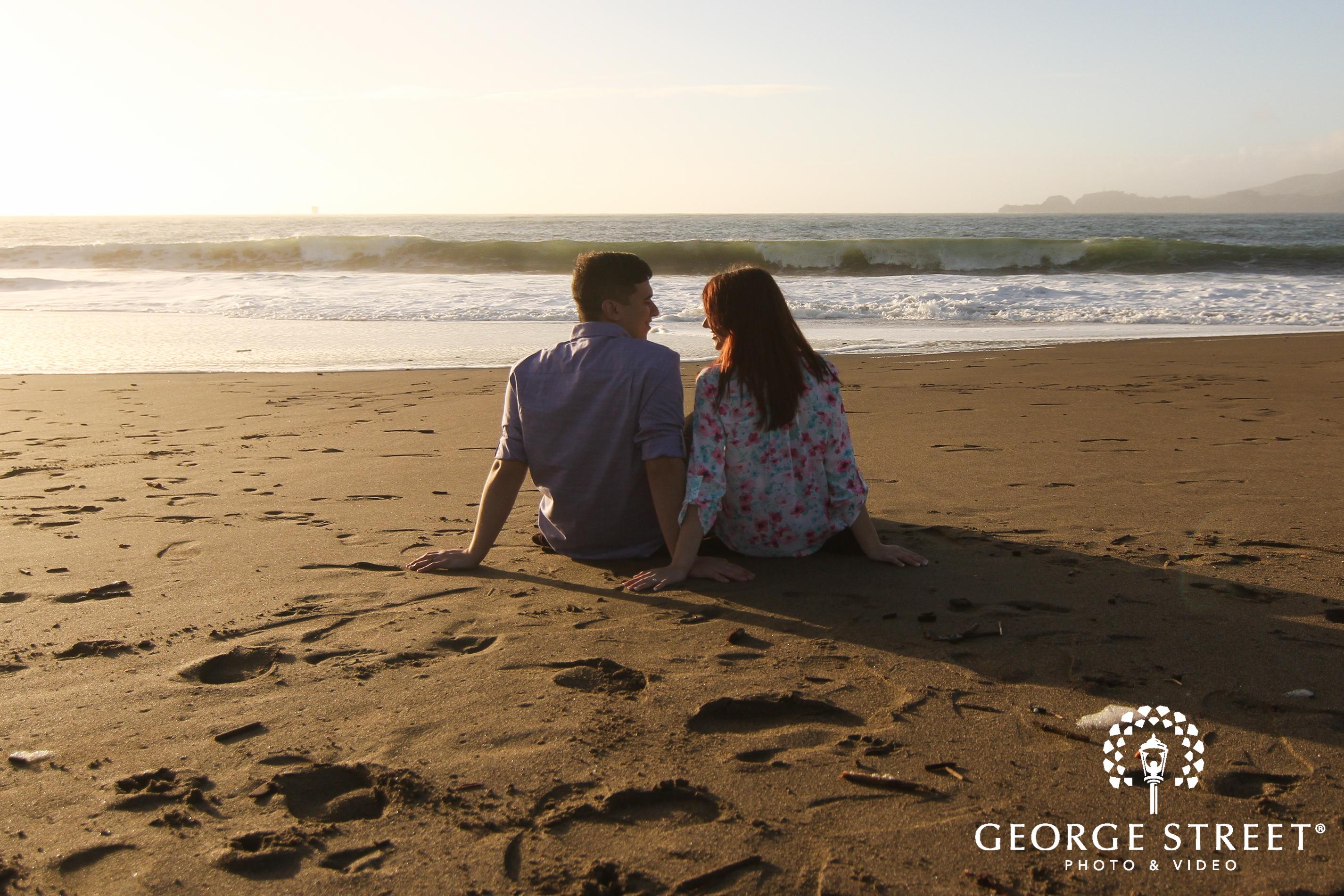couple sitting on sand at beach
